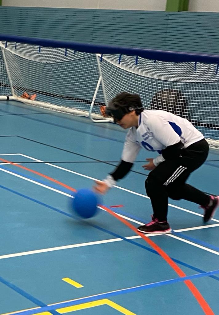 Kuva Azrasta pelaamassa. Azra pelaa seiska laidassa ja on juuri heittänyt palloa. Pallo näkyy kuvassa vasemmalla. Azralla on valkoinen Suomi-paita ja mustat pelihousut.