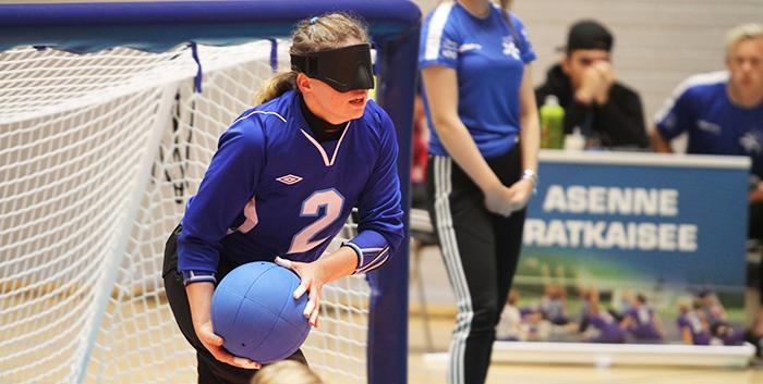 Kuvassa Krista Leppänen on juuri lähdössä heittämään. Krista on seiskalaidassa pallo oikeassa kädessä. Hänellä on sininen Suomi-paita päällään jossa numero 2 sekä mustat pelihousut.
