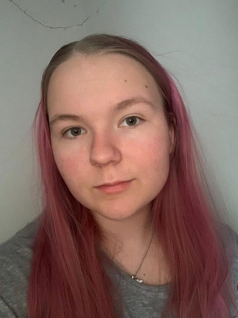 Kasvokuva Jasmin Mikkolasta. Jasminilla on pitkät vaaleanpunaiset hiukset.