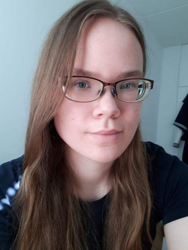 Kasvokuva Miinasta. Miinalla on pitkät ruskeat hiukset ja silmälasit.