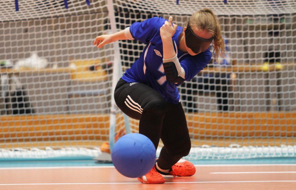 Kuvassa Miina on juuri heittänyt pallon ja pallo näkyy kuvan etuosassa. Miinan hiukset ovat ponin hännällä, hänellä on sininen Suomi-paita jossa numero 7, mustat kyynärsuojat ja oranssit pelikengät.