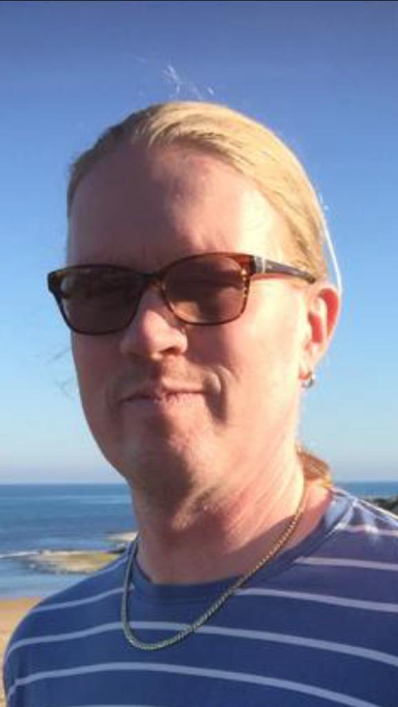 Kasvokuva Artusta. Artulla on pitkät vaaleat hiukset poninhännällä ja aurinkolasit päässä.